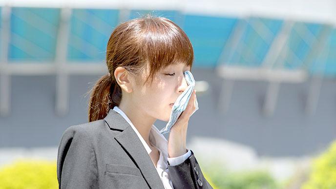 ポケットティッシュで顔を拭く女性