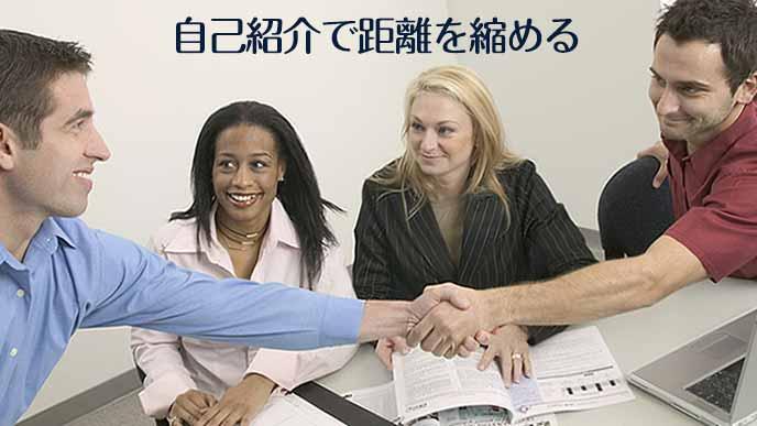 握手する男性社員と見守る会議参加者
