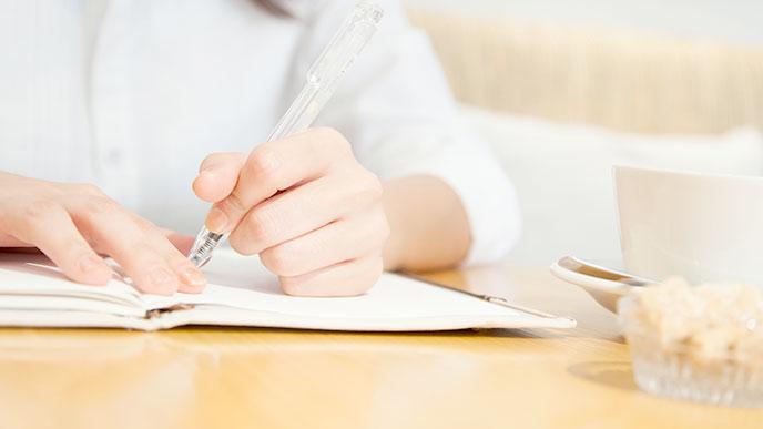 ノートをとる女性の手とコーヒーのカップ