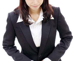スーツを着てお辞儀する女性