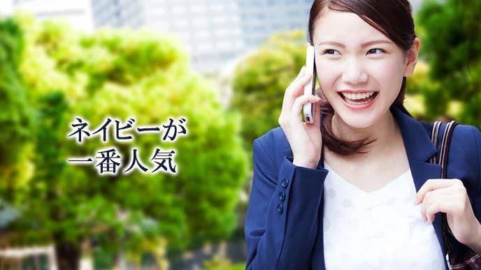 街中で電話連絡する紺色のスーツの営業女性