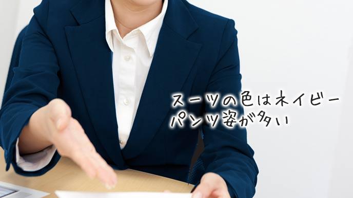 紺色のスーツで営業する女性