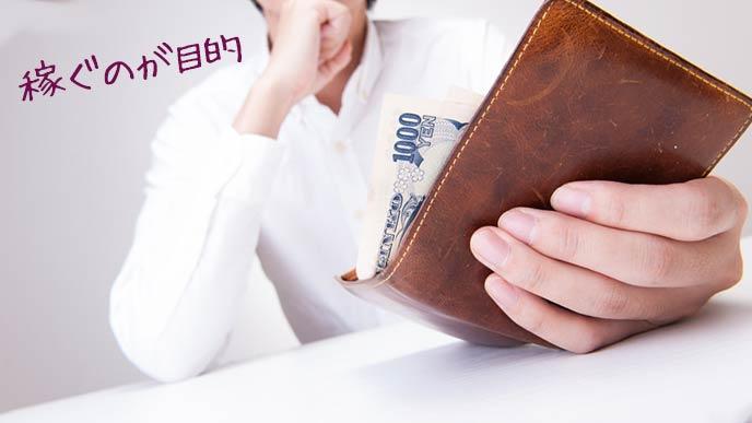 男性が持つ財布から千円札がはみ出る
