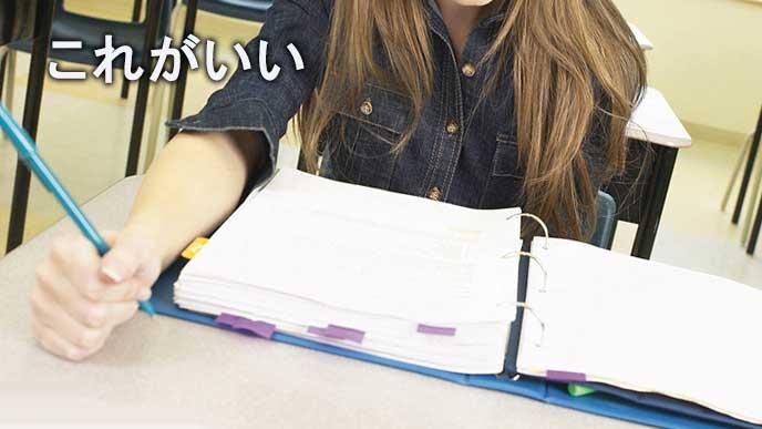 ファイリングされた企業情報を調べる女子大学生