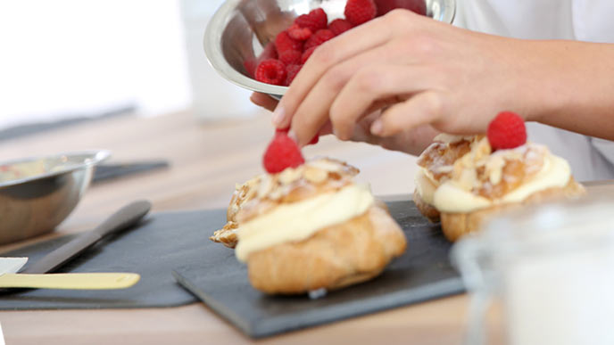 シュークリームにイチゴをのせる女性