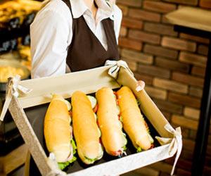 サンドイッチパンを陳列バケットに入れて運ぶ女性バイト