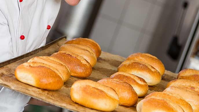 焼きたてパンをトレーに載せて運ぶ