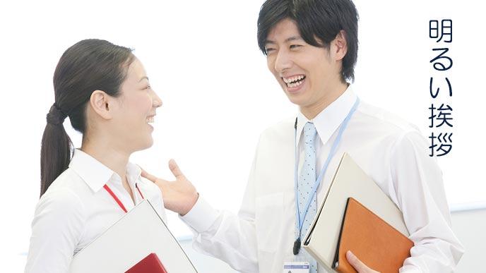 笑顔で女性の同僚と会話する男性社員