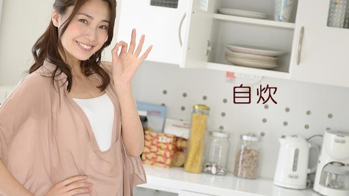 台所でマネーサインを出す女性