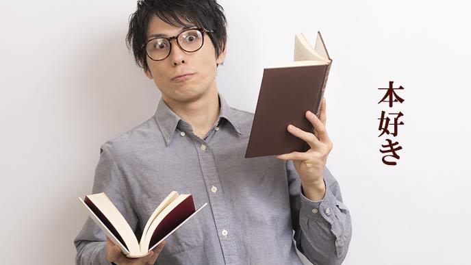 本を両手に持つ男性