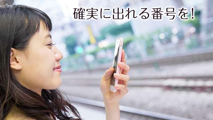 駅のプラットフォームで電話を受ける女性
