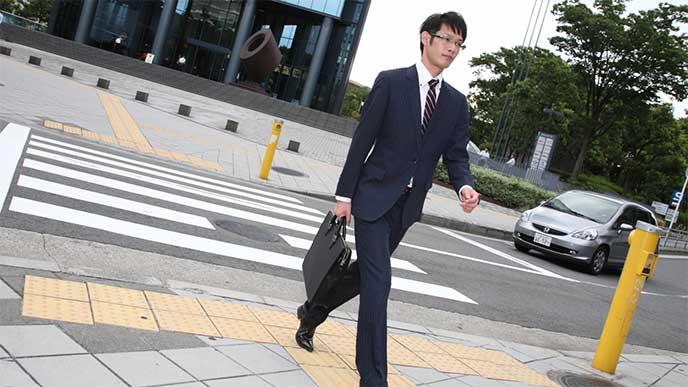 営業に歩くスーツを着た男性