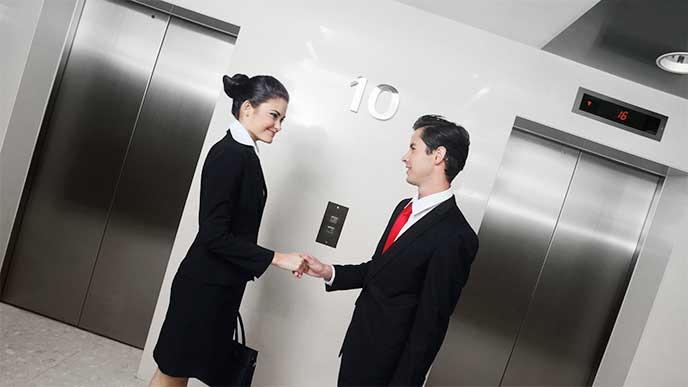 商談がまとまって握手するスーツを着た男女