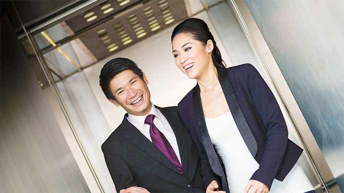 笑顔で話をしてるスーツを着た男女