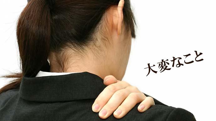 肩を手で押さえる女性事務員