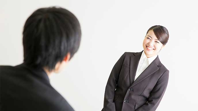 直属の上司に挨拶をするスーツを着た若い女性