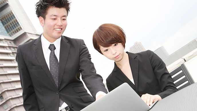 パソコンを見ながら女性と話してる男性社内SE