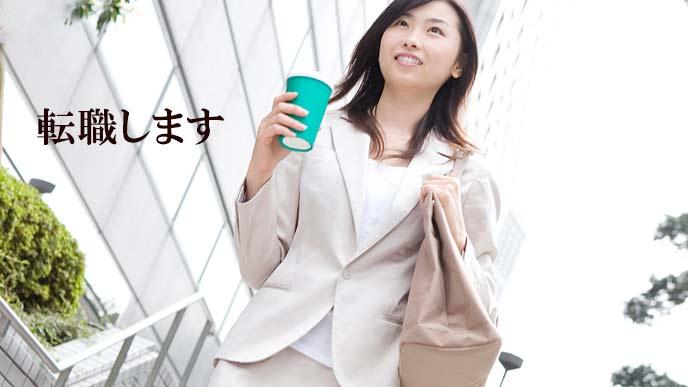 飲み物を持ってビジネス街を歩く女性