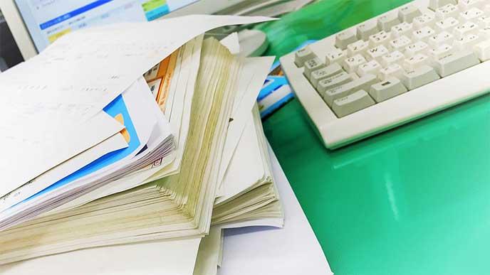 沢山の仕事の書類が積まれたデスク
