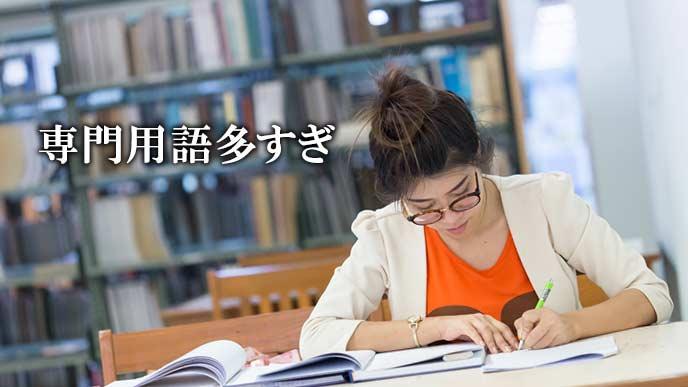 応募書類に専門書を参照しながら記述する女性