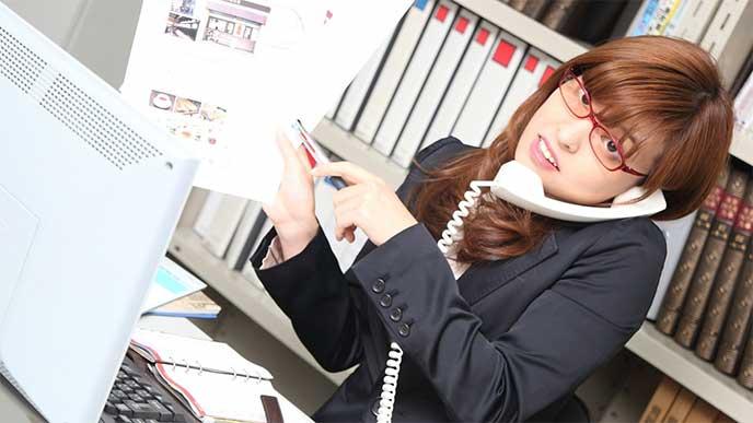 電話をかけながら書類を指差し指示を出してる忙しそうな女性社員