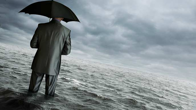 膝まで水に浸かるビジネスマン