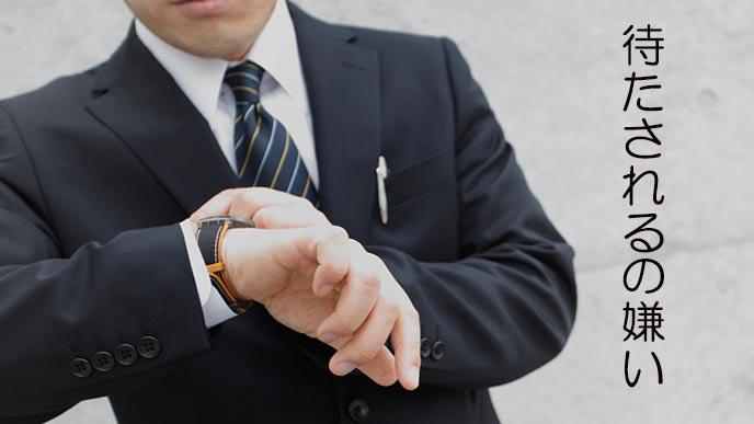 腕時計を見て苛立つビジネスマン