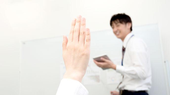 手を上げる女性の手
