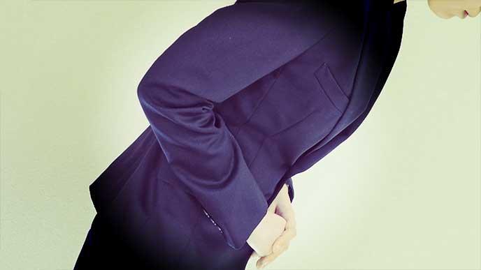 謝罪のため頭を下げてるスーツを着た女性
