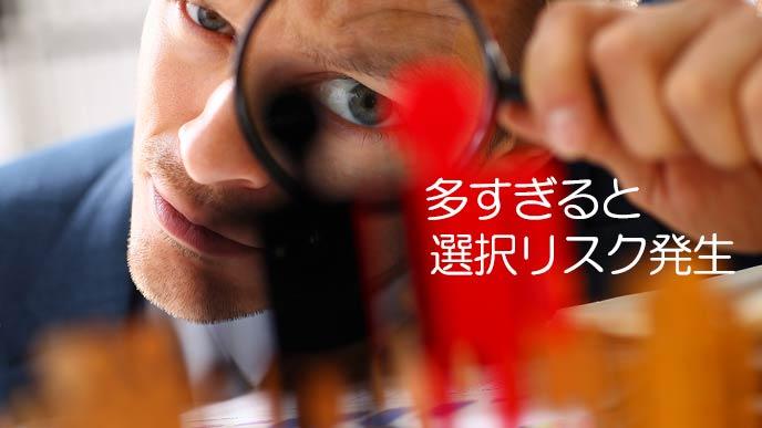 虫眼鏡で駒を見つめる男性