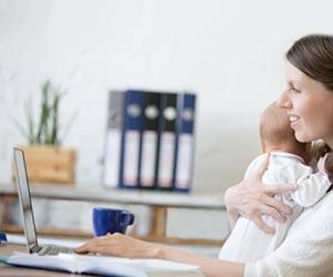 赤ちゃんを抱っこしながら自宅で働く女性