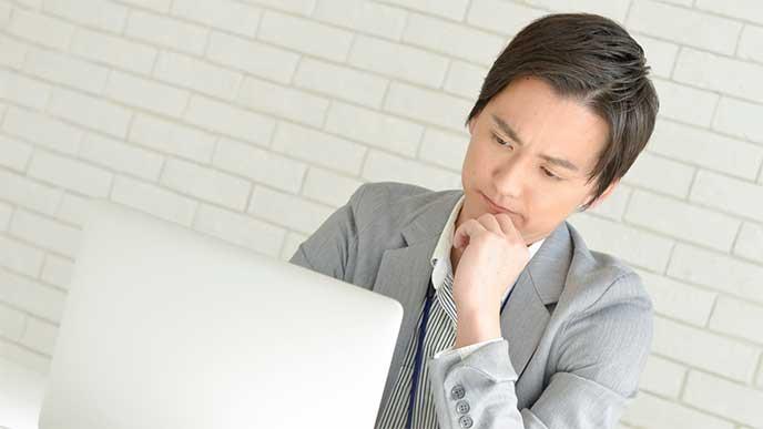 パソコンを見ながら考えているスーツを着た男性