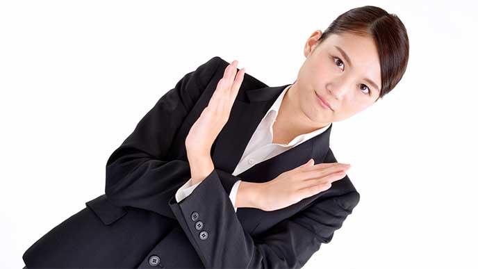 バツサインを手でしてるスーツを着た女性