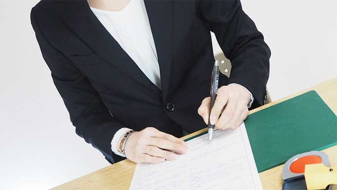 契約書にサインをする女性社員