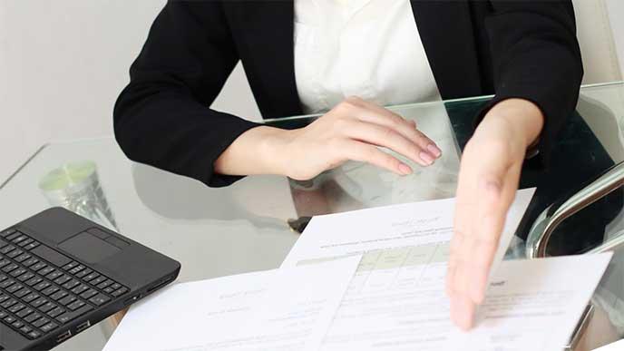 契約書を提示して話をしてる女性社員
