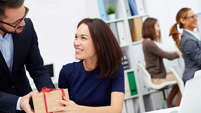 同僚に贈り物を渡す社員