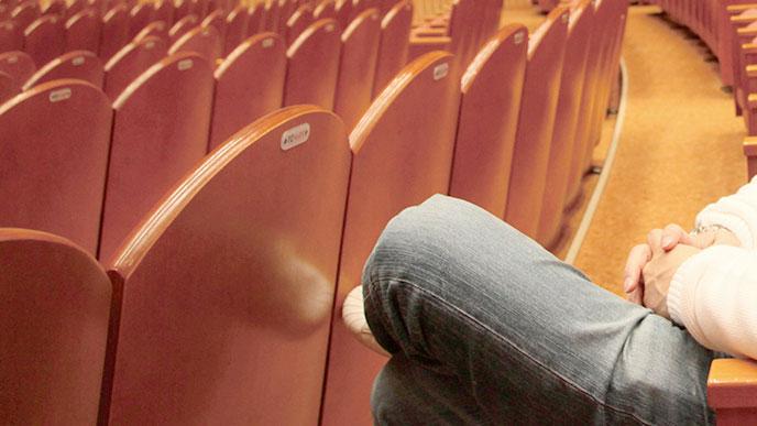 映画館の椅子に座る人