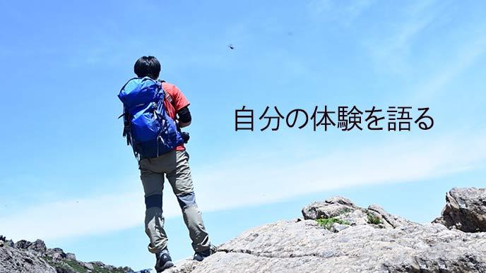 登山して山頂に立つ男性