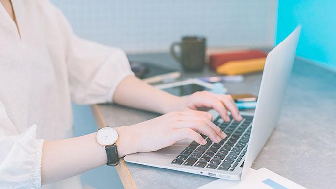 ノートパソコンで字を打つ人の手