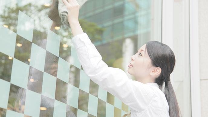 お店の外面を拭く女性