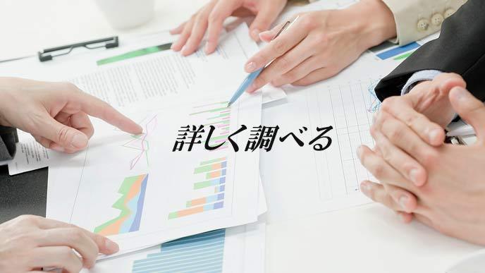 グラフや文書のビジネス資料を調べるビジネスマン
