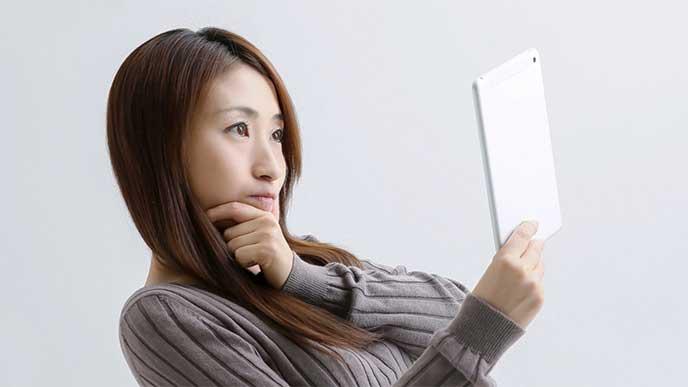 タブレットを使って会社情報を調べてる女性