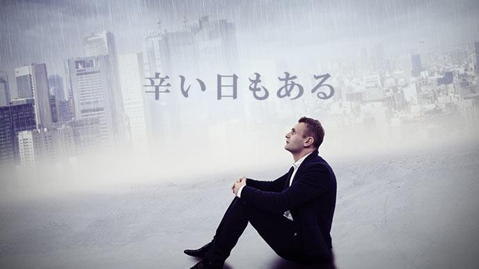 ビル街の雨天を見上げるビジネスマン