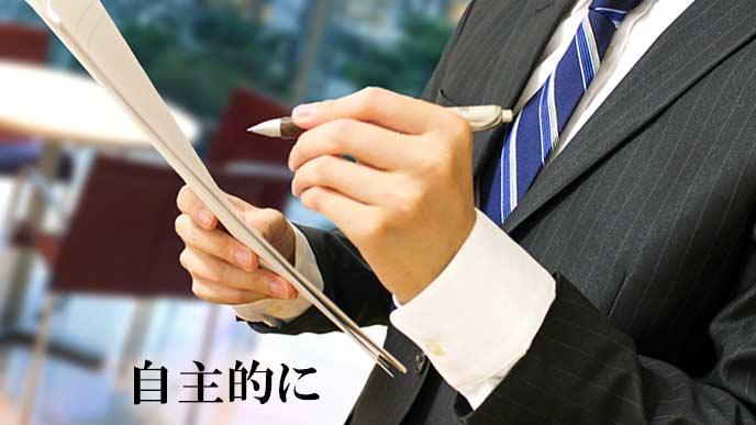 メモ書きしながら書類を見る男性