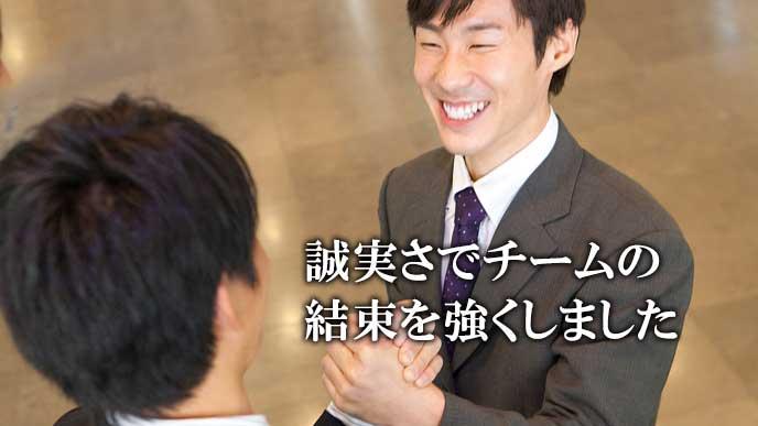 同僚と手を組んで笑顔のビジネスマン