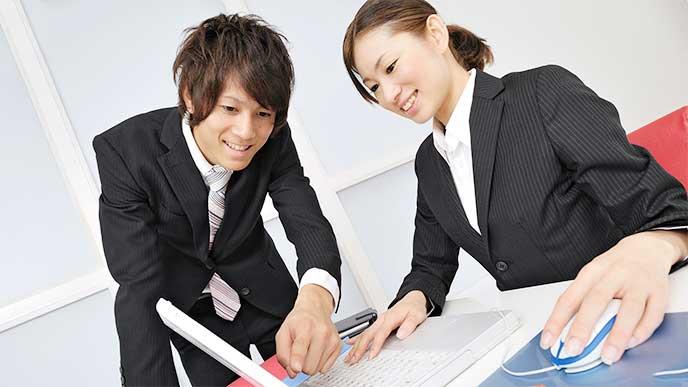 男性社員から仕事を教わる女性新入社員