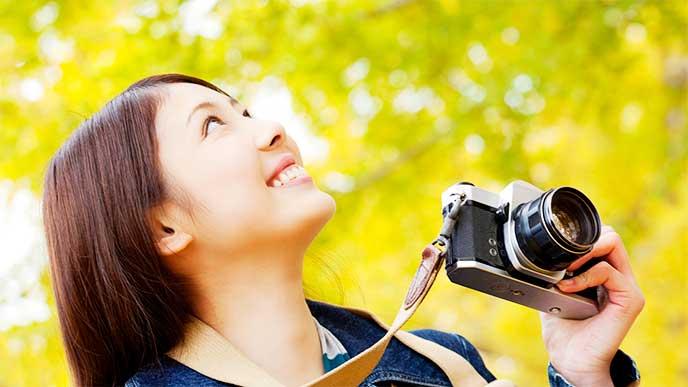 カメラを手に景色を見てる女性