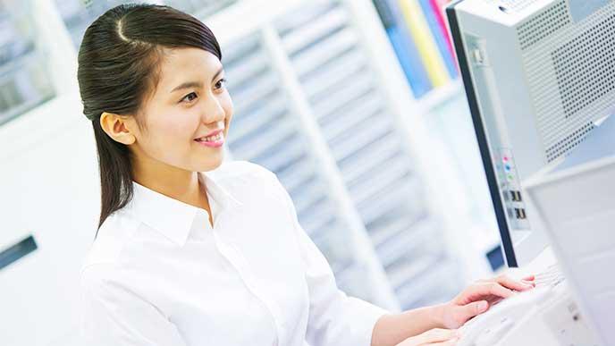 笑顔でパソコンに向かって仕事をしてる女性