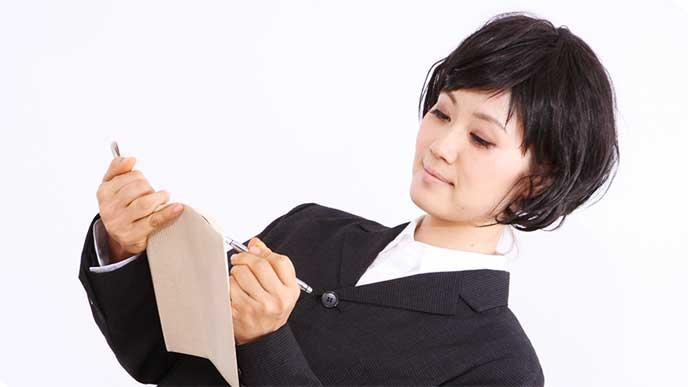 メモを取ってるリクルートスーツを着た女性