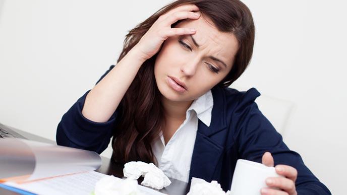 職場のデスクで体調を崩す女性事務員